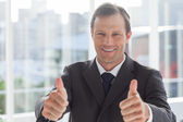 Smiling businessman giving thumbs up — Stock Photo