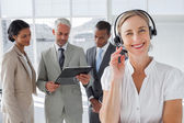 Smiling woman standing with a headset — Stock Photo