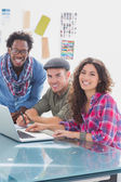 Creative team working together on laptop and smiling at camera — Stock Photo