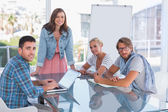 Creative team having meeting and smiling at camera — Stock Photo