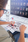 Photo editor making some cuts on the contact sheet — Stock Photo