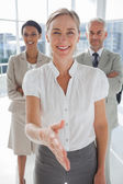 Smiling businesswoman giving a handshake with colleagues behind — Stock Photo