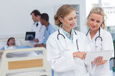 Two women doctors looking at tablet — Stock Photo