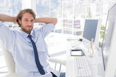 Smiling designer with arms behind head — Stock Photo