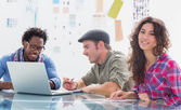 Team of editors at work with one smiling at camera — Stock Photo