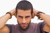 Handsome man posing with hands on head — Stock Photo