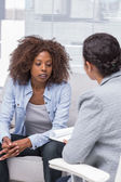 Patient sitting on sofa and talking to therapist — Stock Photo