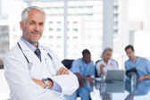Smiling doctor with arms folded — Foto Stock