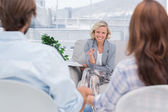Smiling psychologist talking to a couple — Stock Photo