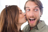 Woman kissing man with beard on the cheek — Stock Photo