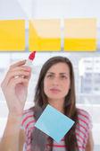 Jovem mulher escrevendo na nota auto-adesiva — Fotografia Stock