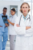 Serious doctor with arms folded — Stock Photo