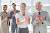 Smiling business applauding together — Stok fotoğraf