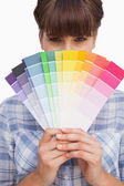 Pretty girl hiding face with colour charts — Stock Photo