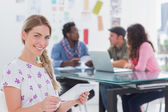 Smiling woman using tablet with creative team working behind — Stock Photo