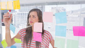 Young woman writing in creative office — Stock Photo