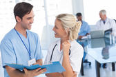 Two young doctors talking about a blue file — Stock Photo