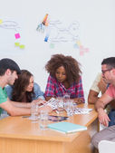 Creative team talking over contact sheets in meeting — Stock Photo