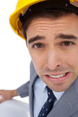 Close up of architect grimacing while holding plans — Stock Photo