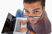 Man wearing glasses sitting on floor using laptop and looking up at camera — Stock Photo