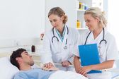 Two women doctors taking care of a patient — Stock Photo