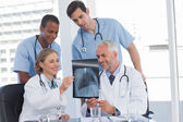 Smiling medical team examining radiography — Stock Photo