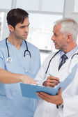 Serious doctors talking about file — Stock Photo