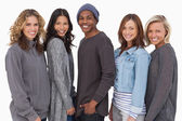 Fashionable young in a row smiling — Stock Photo