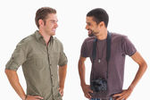 Stylish friends smiling at each other with one holding camera — Stock Photo