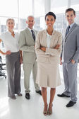 Attractive businesswoman standing in front of colleagues — Stock Photo