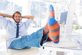 Designer relaxing at desk with no shoes and smiling — Stock Photo