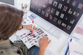 Photo editor making some cuts on contact sheet — Stock Photo