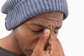Mann in mütze hut wincing mit kopfschmerzen — Stockfoto