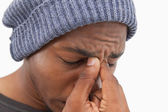 Uomo in beanie cappello trasalendo con un mal di testa — Foto Stock