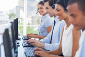 Smiling call centre employees working on computers — Stock Photo