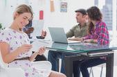 Editor houden tablet pc en glimlachen als haar team werkt achter haar — Stockfoto