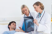 Doctors showing radiography to a patient — Stock Photo