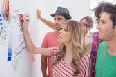 Creative team watching coworker add to flowchart — Stock Photo