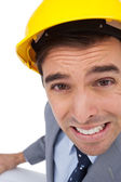Close up of architect with hard hat grimacing while holding plans — Stock Photo