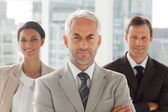 Businessman standing with colleagues behind — Stock Photo