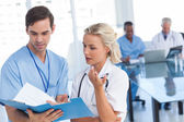 Young doctors talking about a blue file — Stock Photo