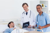 Doctors with radiography standing next to a patient — Stock Photo