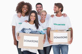 Happy group of volunteers holding clothes donation boxes — Stock Photo