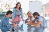 Team having meeting with one woman smiling at camera — Stock Photo