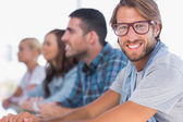 Creative team sitting in a line with one man smiling — Stock Photo