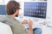 Photo editor looking at thumbnails on computer — Stock Photo