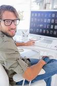 Smiling photo editor at his desk — Stock Photo