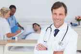 Smiling doctor standing and looking at the camera — Stock Photo
