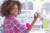 Woman drawing on flowchart with sticky notes and smiling at camera — Stock Photo