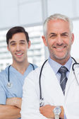 Smiling doctors with arms crossed — Stock Photo